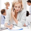 Businesswoman with phone in office — Stock Photo