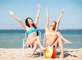 Chicas tomando el sol en las sillas de playa — Foto de Stock