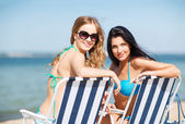 Girls sunbathing on the beach chairs — Stock Photo
