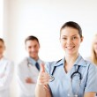 Doctor with group of medics showing thumbs up — Stock Photo #29134485