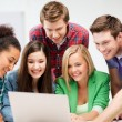 International students looking at laptop at school — Stock Photo #29245897