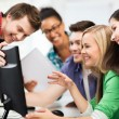 Students looking at computer monitor at school — Stock Photo
