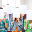 Students covering faces with blank papers — Stock Photo #29245945