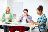 Students looking into devices at school — Stock Photo