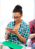 African student browsing in smartphone at school — Stockfoto