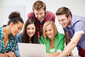 International students looking at laptop at school — Stock Photo