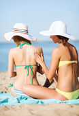 Girls applying sun cream on the beach — Stock Photo