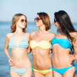 Girls in bikinis walking on the beach — Stock Photo