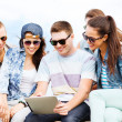 Stock Photo: Group of teenagers looking at tablet pc