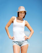 Girl in hat standing on the beach — Stock Photo