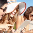 Stock Photo: Girls with tablet pc on the beach
