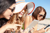 Chicas con tablet pc en la playa — Foto de Stock