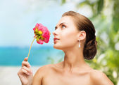 Woman wearing earrings and smelling flower — Stock Photo