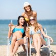 Girls with drinks on the beach chairs — Stock Photo