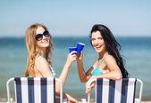 Mädchen mit getränken auf den strand-stühlen — Stockfoto