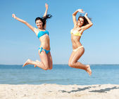 Girls in bikini jumping on the beach — Stock Photo