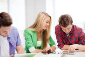 Students browsing in tablet pc at school — Stock Photo