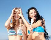 Mädchen in bikinis mit eis am strand — Stockfoto