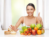 Woman with fruits rejecting junk food — Stock Photo