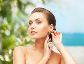Beautiful woman trying on gold earrings — Stock Photo