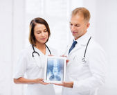 Two doctors showing x-ray on tablet pc — Stock Photo