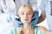 Plastic surgeon or doctor with patient — Stock Photo