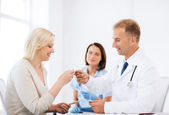 Doctor giving tablets to patient in hospital — Stock Photo