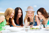 Girls looking at smartphone in cafe on the beach — Stock Photo