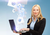 Businesswoman holding laptop with email sign — Stock Photo