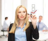 Businesswoman drawing checkmark on virtual screen — Stock Photo