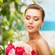 Woman wearing earrings and holding flowers — Stock Photo #30058543