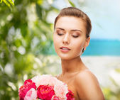 Woman wearing earrings and holding flowers — Stock Photo