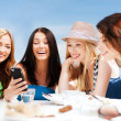 girls looking at smartphone in cafe on the beach — Stock Photo #30060739
