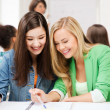 Student girls pointing at notebook at school — Stock Photo