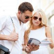 Couple with tourist book in the city — Stock Photo