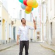 Man with colorful balloons in the city — Stock Photo