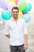 Man with colorful balloons in the city — Stockfoto