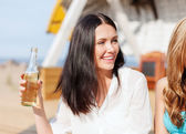 Girl with drink and friends on the beach — Stock Photo