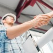 Builder with blueprint shaking partner hand — Foto de Stock