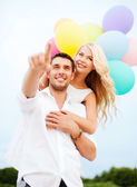 Couple with colorful balloons at sea side — Stock Photo