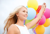 Woman with colorful balloons outside — Stock Photo