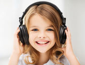 Little girl with headphones at home — Stock Photo