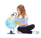 Child looking at globe with magnifier — Stock Photo