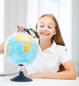 Child looking at globe with magnifier — 图库照片