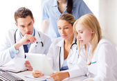 Group of doctors looking at tablet pc — Stock Photo