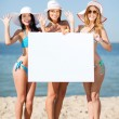 Girls with blank board on the beach — Stockfoto