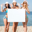 Girls with blank board on the beach — Stok fotoğraf