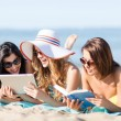 Girls with tablet pc on the beach — Stock Photo #30511387