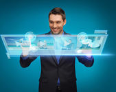 Businessman pressing buttons on virtual screen — Stock Photo