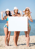 Girls with blank board on the beach — Stock Photo